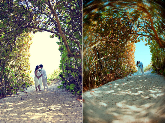Beach bride and groom kiss on beach under romantic arches of trees