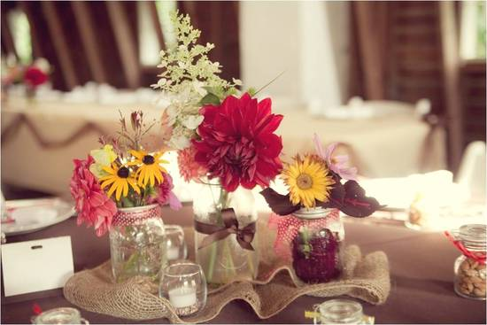 Rustic, country wedding reception tablescape with colorful wild flowers and guest favors in mason ja