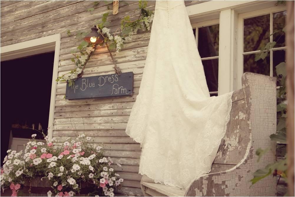 Rustic-michigan-wedding-venue-blue-dress-barn-ivory-lace-wedding-dress-hangs-outside.full