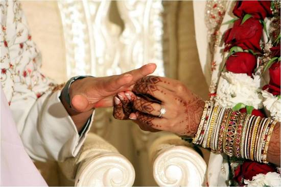 Indian groom slips wedding band on beautiful bride's finger during traditional wedding ceremony