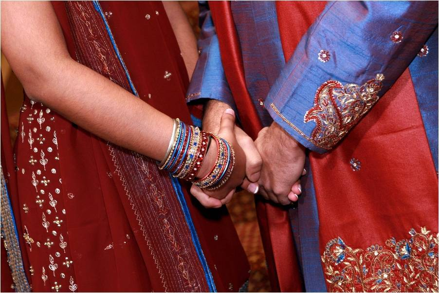Traditional-indian-wedding-gold-red-maroon-blue-color-palette-ornate-bridal-style-wedding-attire-bride-groom-hold-hands.full