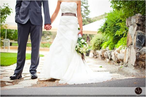 Bride-and-groom-now-newlyweds-hold-hands-white-wedding-dress-ribbon-sash-grey-suit.full
