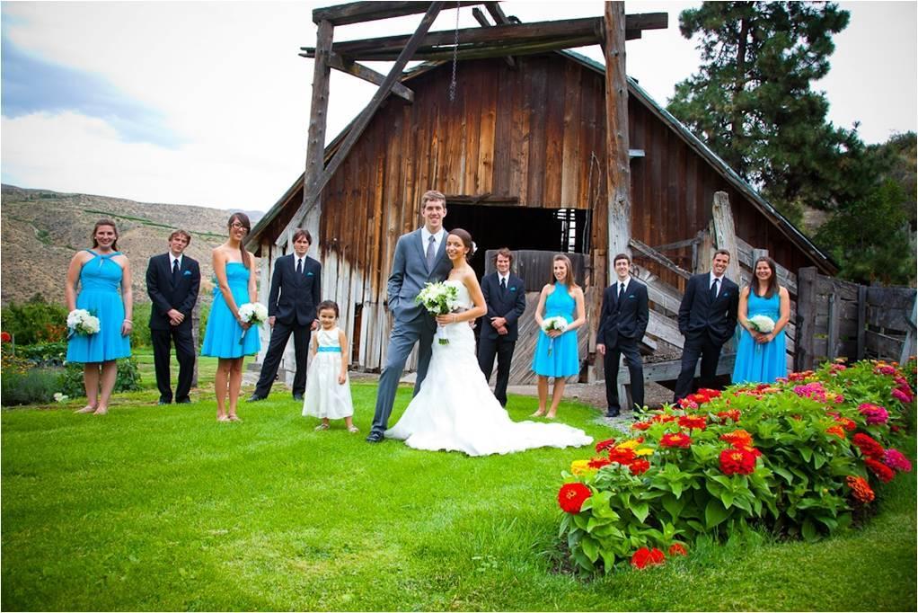 Bride-groom-pose-outside-with-wedding-party-aqua-bridesmaids-dresses-rustic-wedding-venue.full