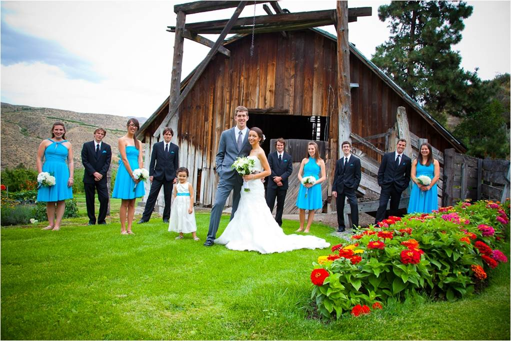 Bride and groom pose outside of rustic wedding venue with ...
