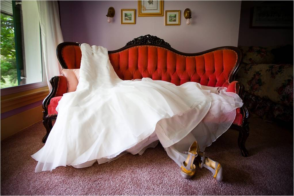 White-strapless-wedding-dress-lays-on-red-vintage-couch-t-strap-bridal-heels.full