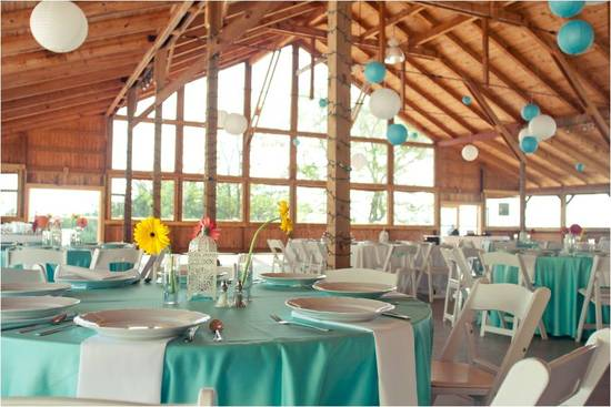 Rustic lodge-like wedding venue in Virginia, decorated with white and teal tableware and paper lante