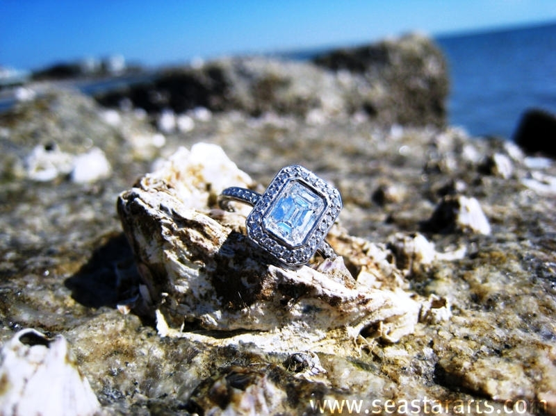 Emerald cut diamond Ritani engagement ring photographed by sea, cliffside