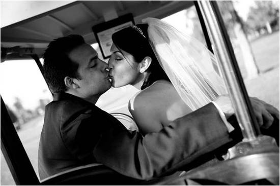 Artistic black and white wedding photo- bride and groom kiss after saying I Do, riding golf cart