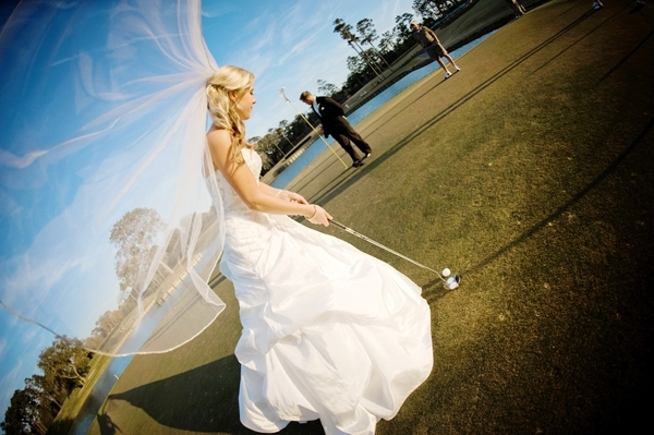 Bride-in-full-wedding-day-garb-veil-blowing-in-breeze-tees-up-and-puts-at-golf-course-wedding.full