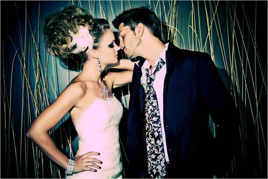Edgy bride in strapless wedding dress, kisses casual, rock n roll groom