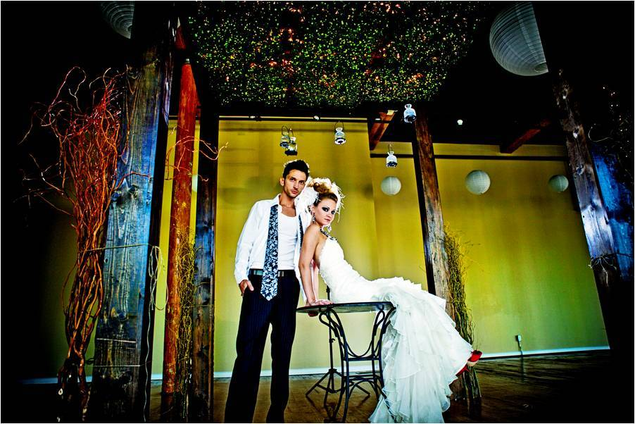 Edgy bride and groom take engagement photos, colorful, industrial backdrop