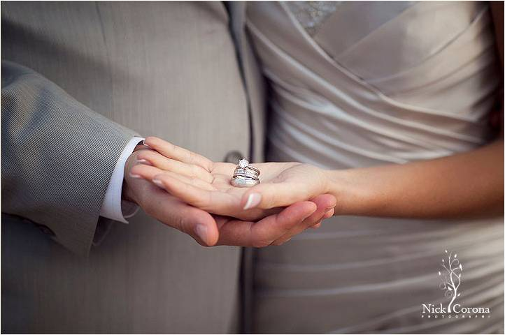 Bride and groom stand together with hands out, holding diamond engagement ring and wedding bands
