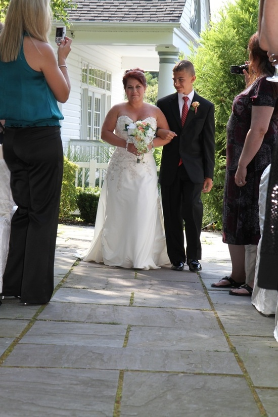 This beautiful, mature red-haired bride walks down the aisle on the arm of her son.