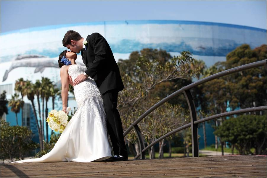 Groom-in-black-tux-dips-bride-holding-ivory-bridal-bouquet-strapless-wedding-dress-with-nautical-backdrop.full