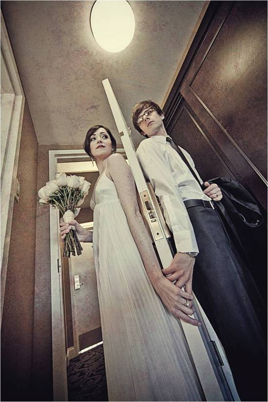 Bride and groom stand on either side of hotel room door before their intimate first look