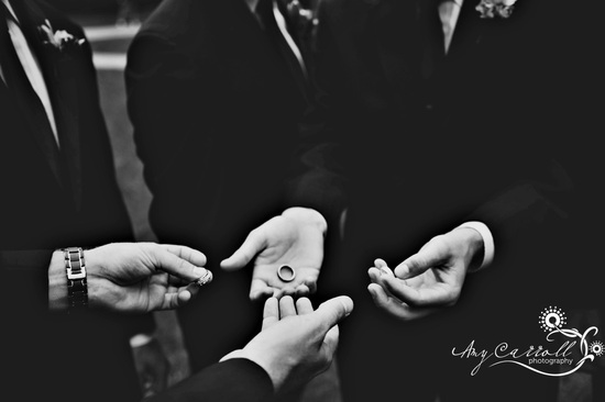Best man and groomsmen, in formal black tuxs, hold wedding bands before wedding ceremony