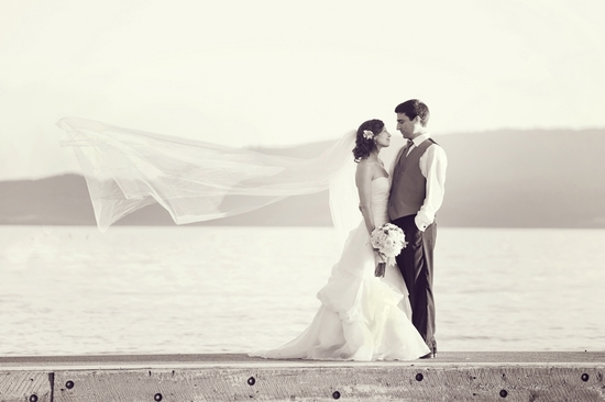 Bride and groom stand on dock with Montana mountains in background, kiss after saying I Do