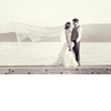 Bride-and-groom-pose-on-dock-brides-traditional-veil-blows-in-breeze.square