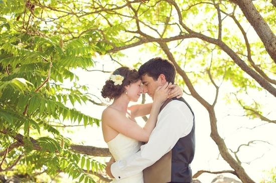 Bride with low wedding hairstyle updo, ivory flower accessory, holds groom under tree