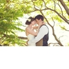 Bride-wedding-hairstyle-low-updo-flower-in-hair-holds-groom-under-tree.square