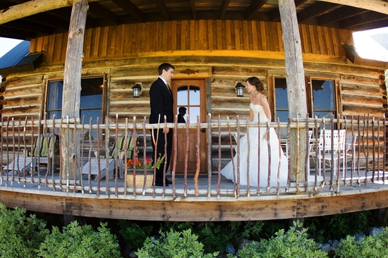 Rustic first look wedding photograph- bride and groom in front of log cabin