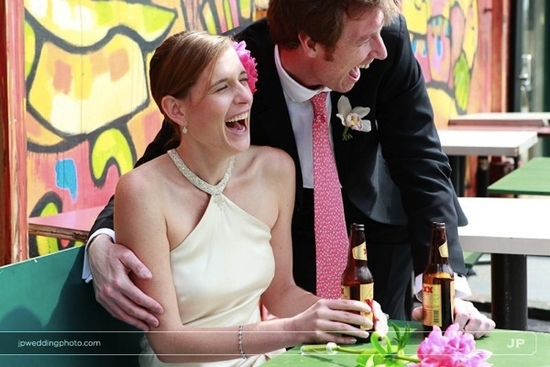 Bride in ivory halter wedding dress laughs with handsome groom while drinking local beers at wedding