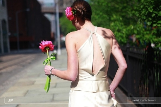 Bride, in ivory sheath wedding dress with keyhole back, holds single fuschia flower for bridal bouqu