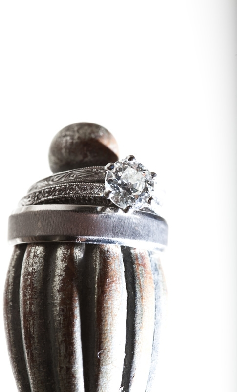 Artistic wedding photograph of engagement ring with round brilliant diamond and pave diamonds, engra