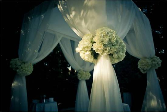 Ivory chuppah adorned with ivory roses for this chic outdoor wedding ceremony