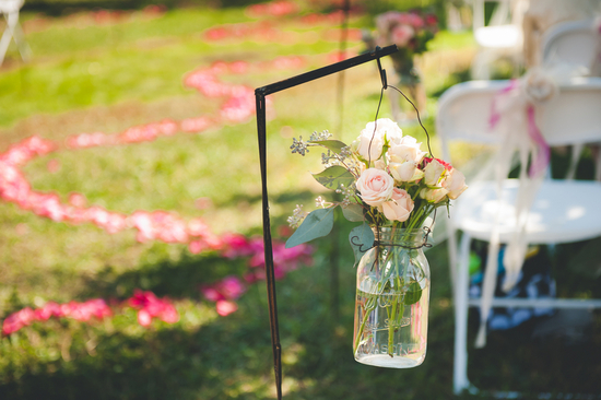 Mason Jar holding Flowers As Aisle Decor