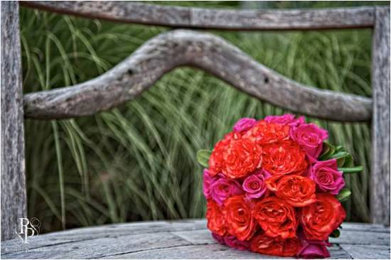 Bride's hot pink and orange rose and daisy bridal bouquet sits on wood bench