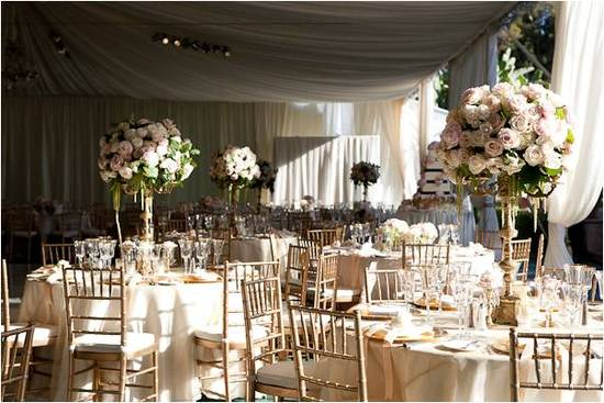 Stunning romantic wedding reception tent with golds, ivories, and blush pinks, high floral topiaries