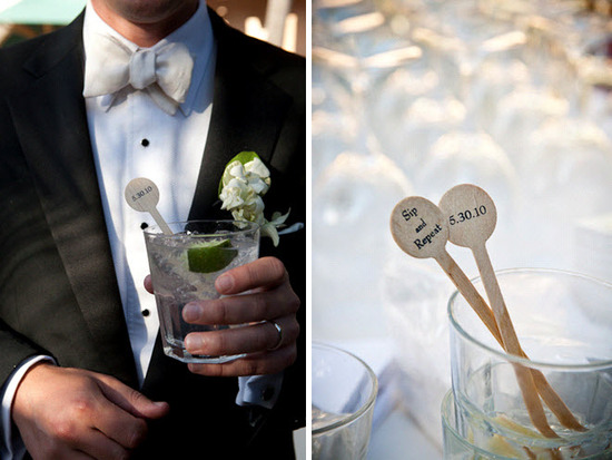 Groom wears black tux, ivory bowtie, white shirt, holds cocktail with personalized stir stick