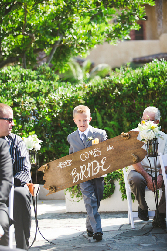 Ring Bearer with a Wooden Here Comes the Bride Sign
