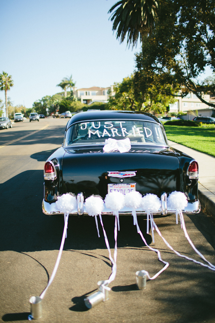 vintage just married car with tin cans and pom poms