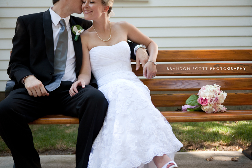 Bride In White Lace Wedding Dress Sits With Der Groom Black Suit On Park Bench