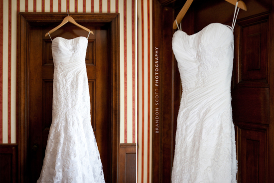 Brides white lace strapless wedding dress hangs on door, ready for the bride to get dressed