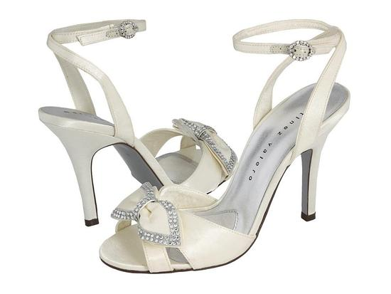 Open toe ivory strappy bridal heels with rhinestone details on lovely bow