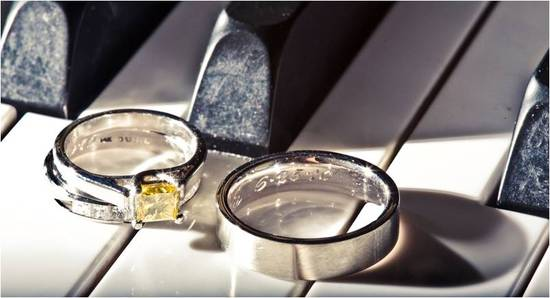 Engagement ring and wedding band atop white and black piano keys