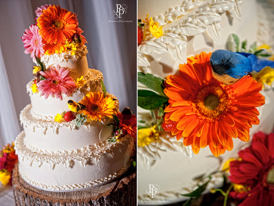 Stunning ivory 4-tier wedding cake adorned with hot pink and orange daisies
