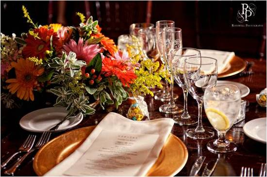 Wedding detail shot- wedding reception tablescape with gold charger plates and bright floral arrange