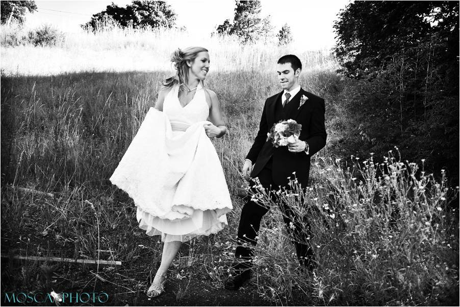 Artistic black and white wedding photo- bride and groom walk through rustic Oregon forest in full we