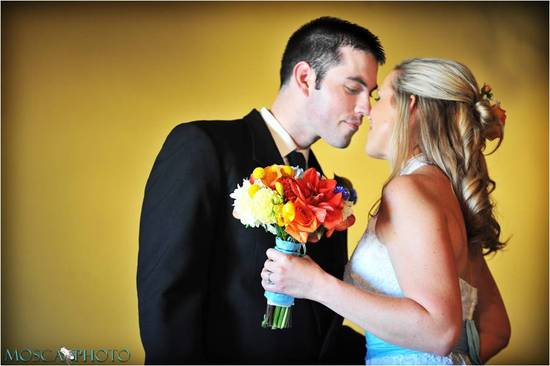 Bride in lace halter wedding dress, holds vibrant bridal bouquet, kisses groom in traditional black