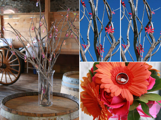 Rustic branches decorated with pink and orange flowers; diamond engagement ring sits atop orange ger