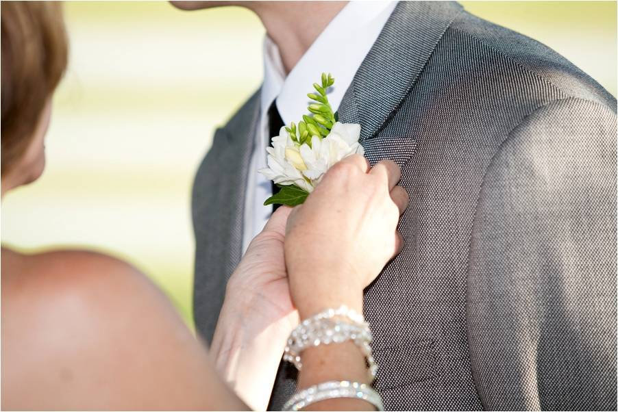 Bride-pins-white-green-floral-boutinierre-on-grooms-lapel-grey-morning-suit-white-shirt-grooms-attire.full