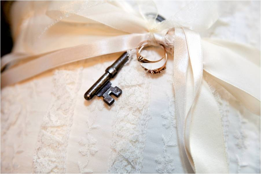 Wedding detail shot- ivory lace Priscilla of Boston wedding dress with key and wedding bands