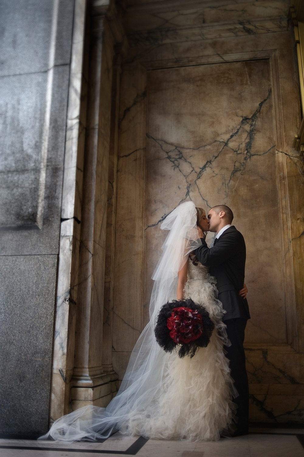 Bride-groom-kiss-outside-of-regal-downtown-la-building-bride-holds-statement-bridal-bouquet-red-roses-black-feathers.full