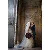 Bride-groom-kiss-outside-of-regal-downtown-la-building-bride-holds-statement-bridal-bouquet-red-roses-black-feathers.square