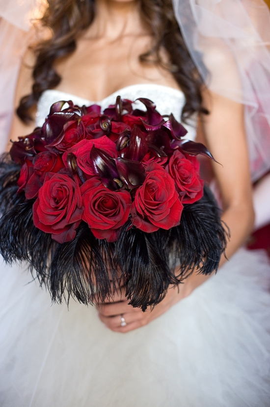 Bride's statement bridal bouquet created with deep red roses and black feathers