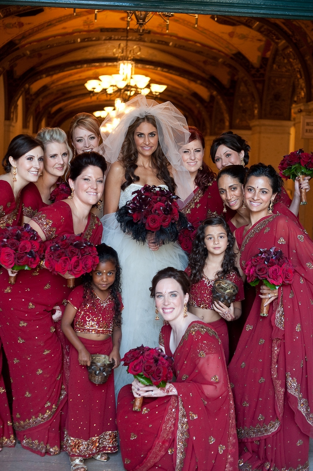 Bride-in-beaded-strapless-wedding-dress-surrounded-by-bridal-party-bridesmaids-flower-girl-in-traditional-red-gold-saris.full